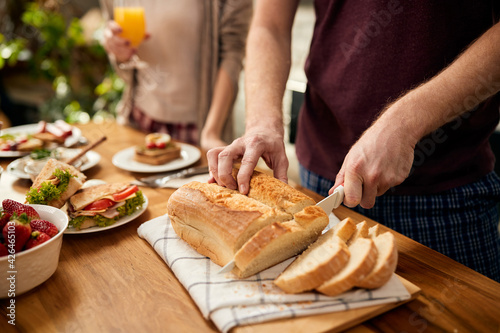 Canvas Close-up of man slicing bread at dining table.
