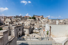 Old Stones Buildings And Ancient Italian Village In Matera In Italy. Panoramic Picture Of White Buildings Made With Stones. Cluster Of Houses. Matera, Italy. Blue Sky.