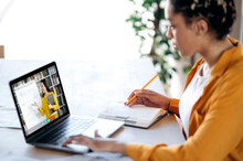 Distance Learning, Online Lecture. African American Female Student Studying At Home Using A Laptop, Listening To An Online Lesson, On The Laptop Screen Female Teacher Shows Information On A Whiteboard