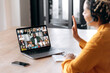 Online business group brainstorm by video conference. Side view of african american young woman, communicates with business partners by video call uses laptop, multiracial colleagues on laptop screen