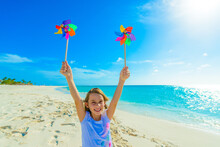 Young Girl At The Beach, Playing With Windmill, Pinwheel On The Sand, Dressed In Colorful Tropical Outfit