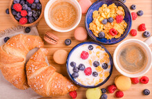 Espresso Coffee With Froth, Croissants, Muesli With Berries And Milk. Delicious Healthy Breakfast. Flakes And Sweet Pastries. High Quality Photo