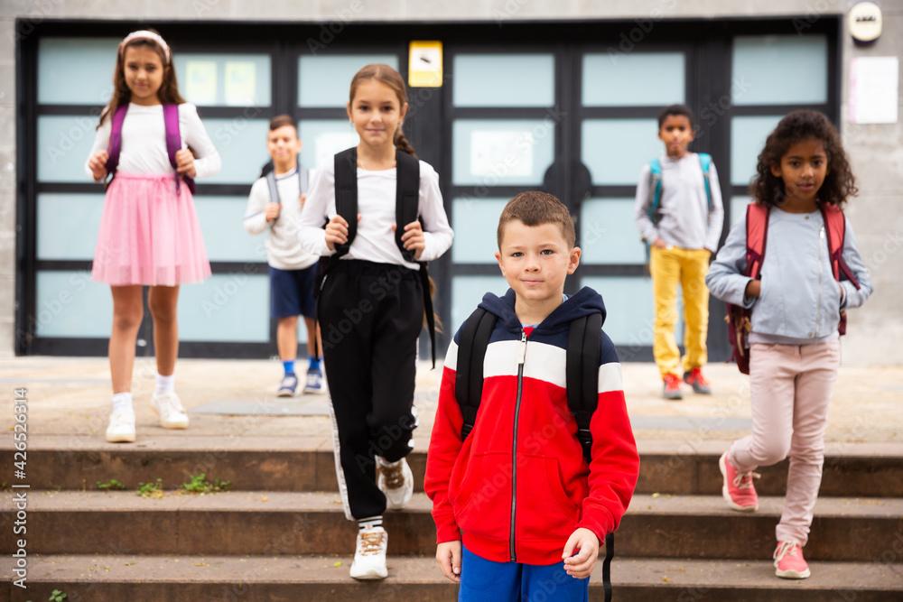 Fototapeta Portrait of positive boy standing near school, children on background