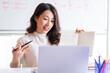Asian female teacher teaching online at home