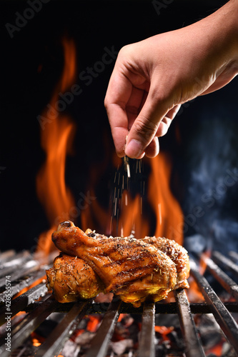 Fototapeta Hand sprinkling salt and spices on grilled chicken leg on the flaming grill