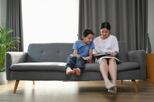 Two Young Asian Girl Watching Funny Video On Digital Tablet While Sitting On Sofa.