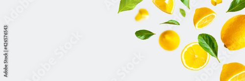 Fototapeta Juicy ripe flying lemons, green leaves on light gray background. Creative food concept. Tropical organic fruit, citrus, vitamin C. Lemon whole and sliced. Summer minimalistic bright fruit background obraz