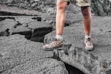 Hiking Shoes Man Hiker On Hawaii Island Lava Rock Hike Climbing Over Big Open Crack In Ground. Summer Travel Adventure Lifestyle.