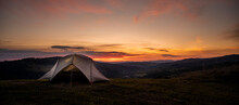 Tourist Tent In The Mountains Under Dramatic Evening Sky. Colorfull Sunset In Mountains. Camping Travell Concept. Traveler People Enjoying The Advanture Alternative Vacation