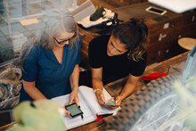 High Angle View Of Female Colleagues Discussing Over Smart Phone In Retail Store