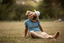 Dad And Daughter In Summer Park Sit On The Grass. Girl Hugs And Kisses The Dad, Father Smiles And Happy. Family Leisure Concept, Nature Walk, Family Care And Values, Fatherhood, Fathers Day