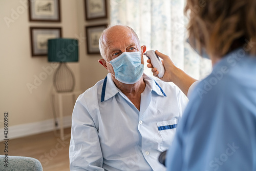 Obraz Nurse checking patient ear temperature during covid pandemic - fototapety do salonu