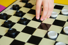 Children Play Checkers On A Colorful Table. Boy And A Girl Compete In Board Games.