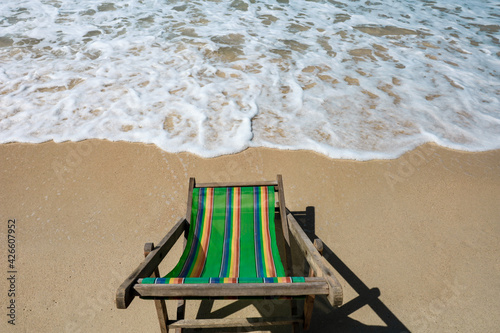 Fotografering Green Deck chair at the tropical sandy beach with blue wave and clear sky in sum