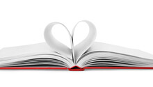 Open Book With Pages Folded In Heart On White Background, Closeup