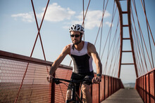 Young Cyclist Pedals On A Red Bridge Outdoors Wearing Sunglasses And Helmet