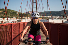 Young Female Cyclist Pedals On A Red Bridge Outdoors Wearing Sunglasses And Helmet