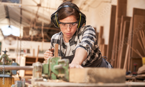 Leinwand Poster Woman as a carpenter or craftsman in workshop