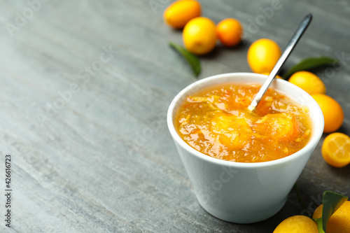 Canvastavla Delicious kumquat jam in bowl and fresh fruits on grey table, space for text