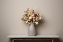 Beautiful Dried Flower Bouquet In Ceramic Vase On White Table Near Light Grey Wall