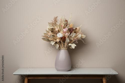 Fotografie, Obraz Beautiful dried flower bouquet in ceramic vase on white table near light grey wa