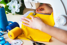 Modern, Professional Sewing Machine With Bright Accessories In The Form Of Measuring Tape, Threads And Yellow Textiles. Seamstress's Hands