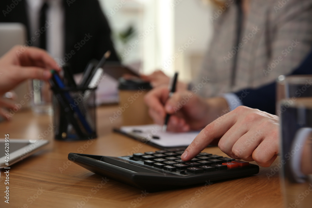 Fototapeta Man using calculator at table in office during business meeting, closeup. Management consulting