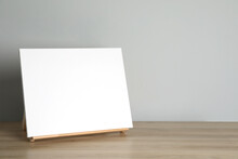 Wooden Easel With Blank Canvas On Table. Space For Text
