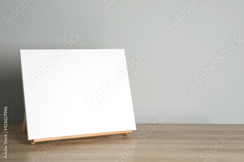 Wooden easel with blank canvas on table. Space for text Fototapet