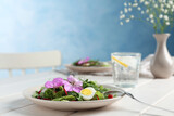 Fresh spring salad with flowers served on white wooden table