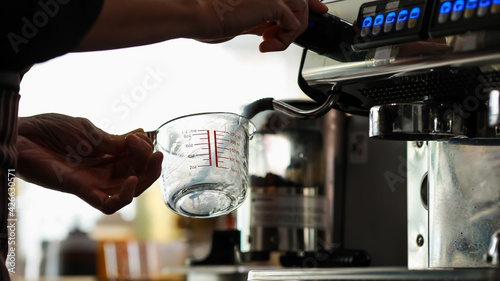 Fotografía Close up shot of clear measuring glass holding by left hand of barista while pou