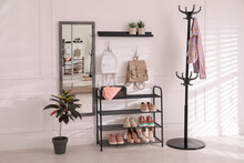 Black Shelving Unit With Shoes And Different Accessories Near White Wall In Hall. Storage Idea