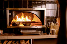 Pans Standing In Oven With Fire In A Restaurant