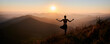 Panoramic view. Back view of slim woman in black sportswear doing yoga exercise on one leg in mountains. Concept of yoga time at sunset.