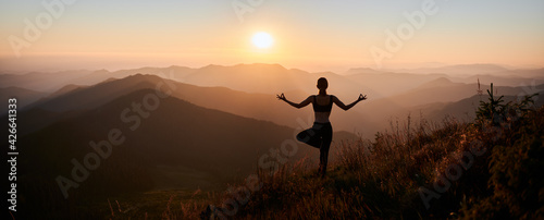 Panoramic view. Back view of slim woman in black sportswear doing yoga exercise on one leg in mountains. Concept of yoga time at sunset. - fototapety na wymiar