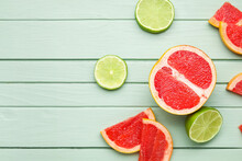 Fresh Sliced Grapefruit And Lime On Color Wooden Background