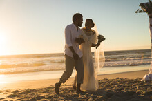 African American Couple In Love Getting Married, Walking On Beach Holding Hands At Sunset