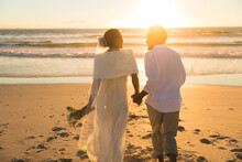 African American Couple In Love Getting Married, Walking On Beach During Sunset Holding Hands