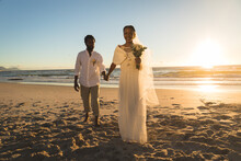 African American Couple In Love Getting Married, Walking On Beach Holding Hands
