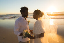 Happy African American Couple In Love Getting Married, Holding Hands On Beach During Sunset