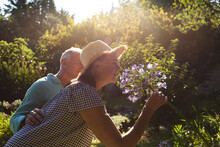 Happy Caucasian Senior Couple Walking In Sunny Garden, Smelling Flowers
