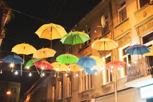 Many Colorful Umbrellas Hang On The City Streets At Night.