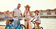 Joyful Family Riding Bicycles Along Wooden Promenade