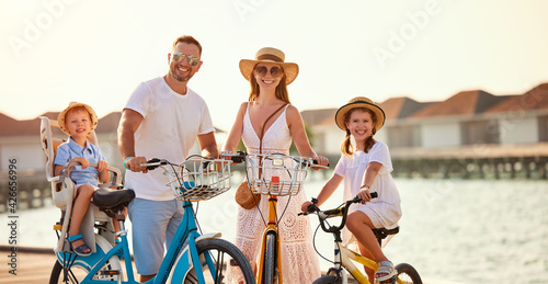 Photo Joyful family riding bicycles along wooden promenade