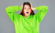 Shocked Amazed Young Woman With Hands On Head Standing And Shouting Over Gray Background