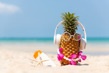 Summer In The Party.  Hipster Pineapple Fashion In Sunglass And Listen Music With Sunblock And Sandal On The Sand Beach Beautiful Blue Sky Background.  Creative Art Fruit For Tropical Style