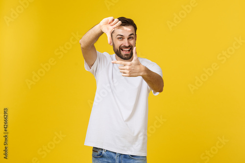Canvas Print Handsome Irish redhead man with beard wearing glasses over yellow isolated background smiling making frame with hands and fingers with happy face