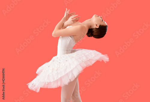 Fototapeta Beautiful young ballerina on color background