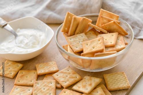 Fototapeta Bowl of tasty crackers and sauce on table obraz