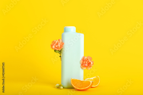 Shower gel, orange slices and flowers on color background